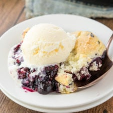 A scoop of blueberry cobbler on a plate topped with a scoop of vanilla ice cream