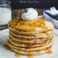 A stack of pancakes on a plate topped syrup and whipped cream