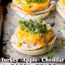 A close up of food on a pan, with bagels topped with sliced turkey, melted cheese and green herbs