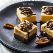 Close up of fudge squares on a plate with  a walnut and drizzled chocolate sauce
