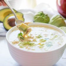 A bowl of soup on a table  with a white cream base, chicken and avacado