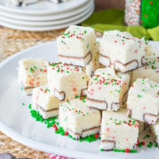 Small squares of white fudge on a plate, with red and green sprinkles on top