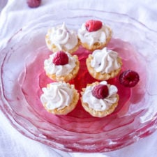 Small tarts sitting on a clear glass plate topped with whipped cream and raspberries