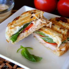 A Turkey Caprese Panini cut in half and displayed on a plate