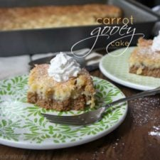 A plate with a slice of Carrot gooey Cake topped with whipped cream