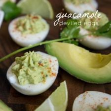 A close up of a Guacamole Deviled Egg next to a sliced quarter of avocado and slices of lime