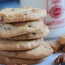 A close up of cookies stacked on a table, with pecans