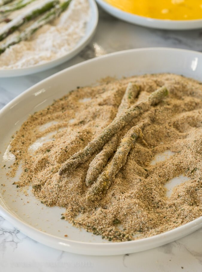 Roll the asparagus spears in flour, eggs and then seasoned breadcrumbs before placing into the air fryer to get nice and crispy.