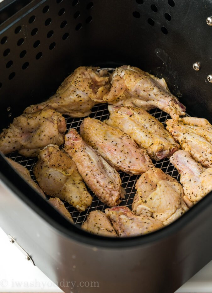 Place the seasoned wings in your air fryer and watch how crispy and juicy they become!