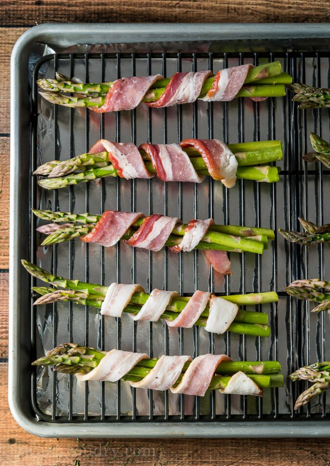 Wrap the asparagus with a skinny strip of bacon and place on a rack in a baking sheet.