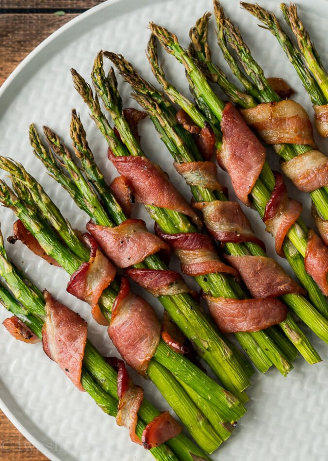 OMG! This Bacon Wrapped Asparagus Recipe is seriously so delicious! We served this easy side dish with steaks and mashed potatoes and it was a total hit!