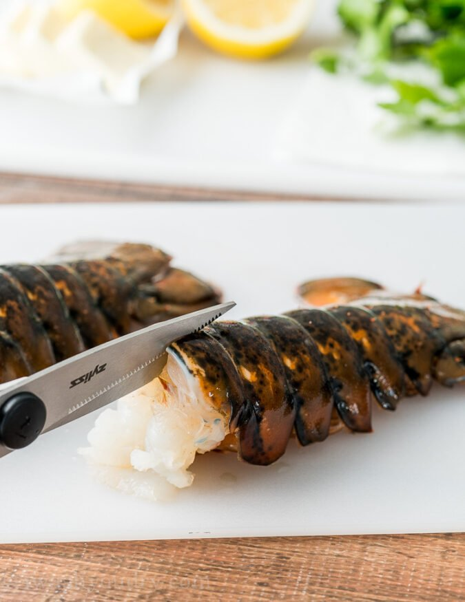 First thing you're going to want to do is use some sharp kitchen scissors to cut down the middle of the lobster shell, just until you get to the fins.