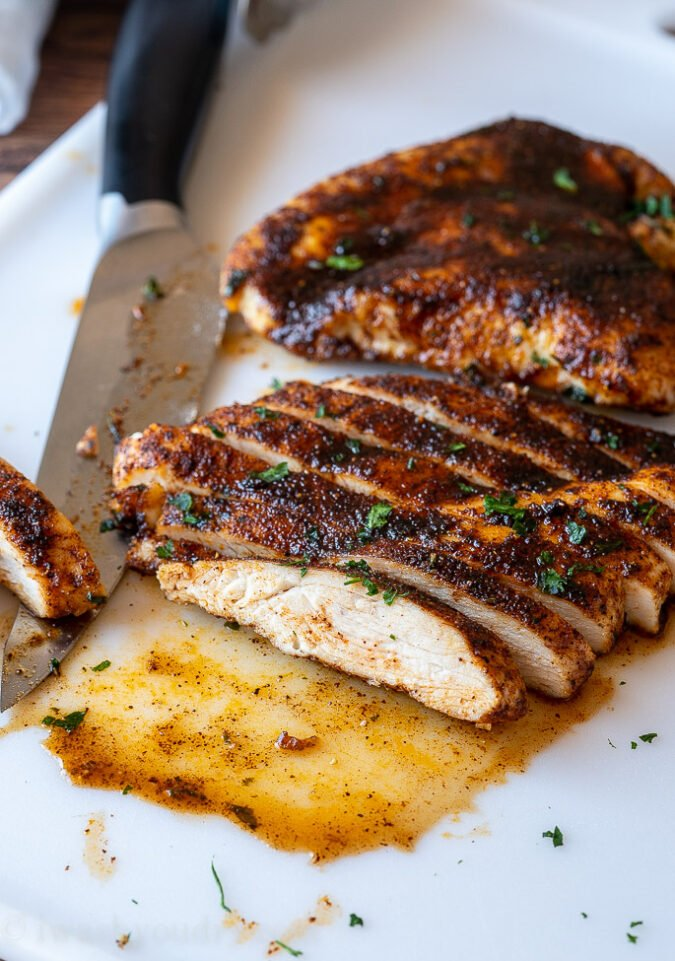 Cooked and sliced chicken breast on a white cutting board.