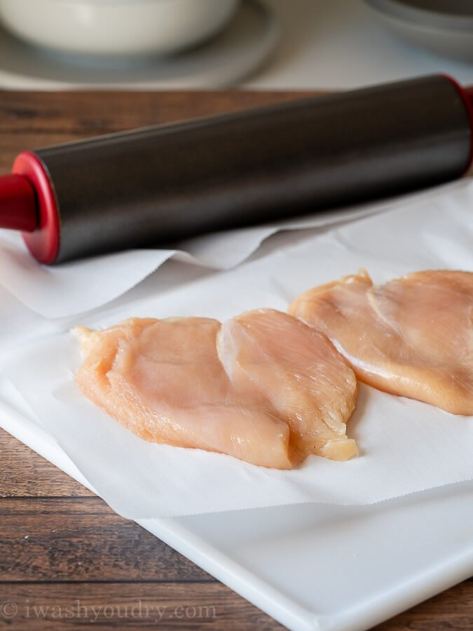 Chicken Breast on cutting board that have been pounded to an even thickness.