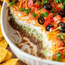 7 Layer Bean Dip with scoop taken out to show layers of beans, guacamole, sour cream and cheese.