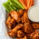 Saucy Buffalo Wings in basket with celery and carrots and a side of ranch dressing