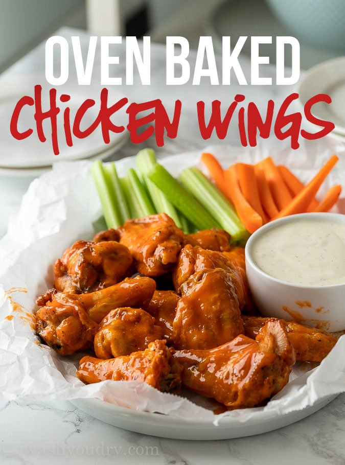 Crispy Oven Baked Chicken Wings covered in buffalo sauce along with celery and carrot sticks.