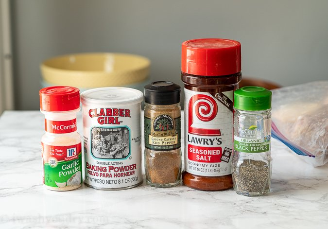 Spices lined up on counter, used for coating baked chicken wings.