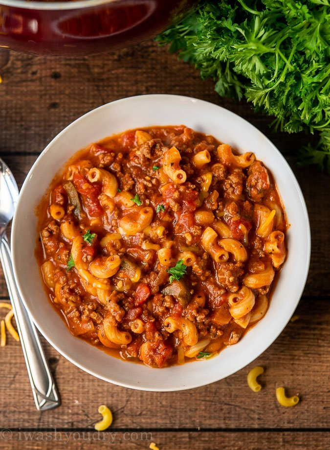 Classic American Goulash in a white bowl with spoon on the left.