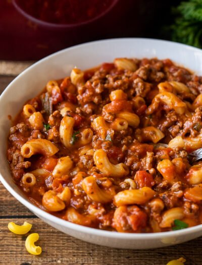 Tender macaroni pasta in a beef and tomato sauce in a white bowl.