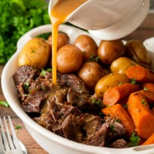 Pouring gravy over shredded beef pot roast in white dish.