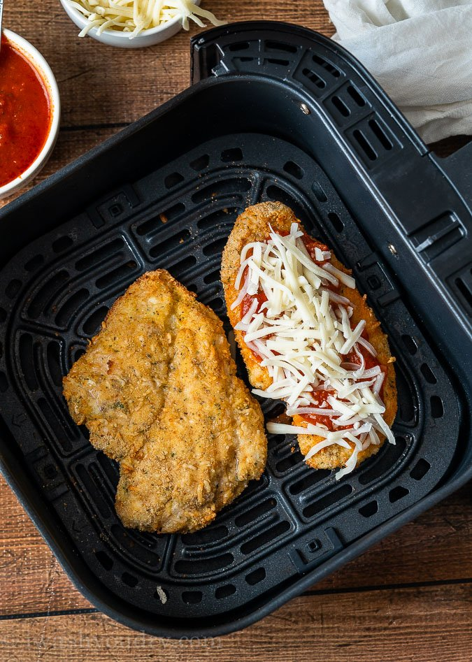 Crispy Chicken Parmesan in the air fryer with marinara sauce and cheese on top.