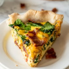 Bacon Cheddar Quiche Recipe : slice of quiche on white plate.