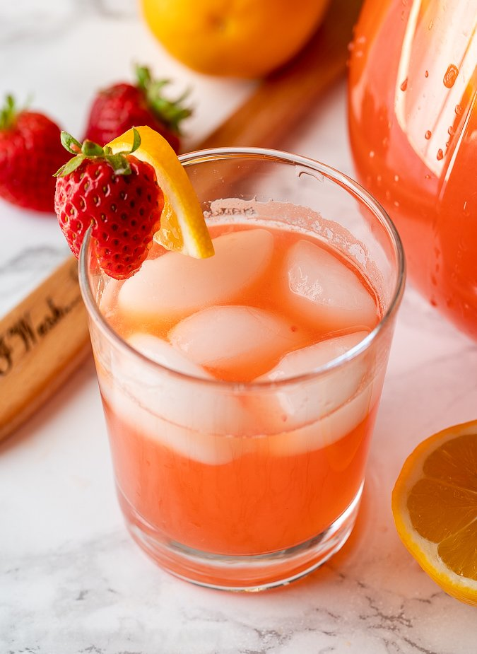 Clear glass full of strawberry lemonade with ice. Garnished with fresh strawberries and a lemon slice.