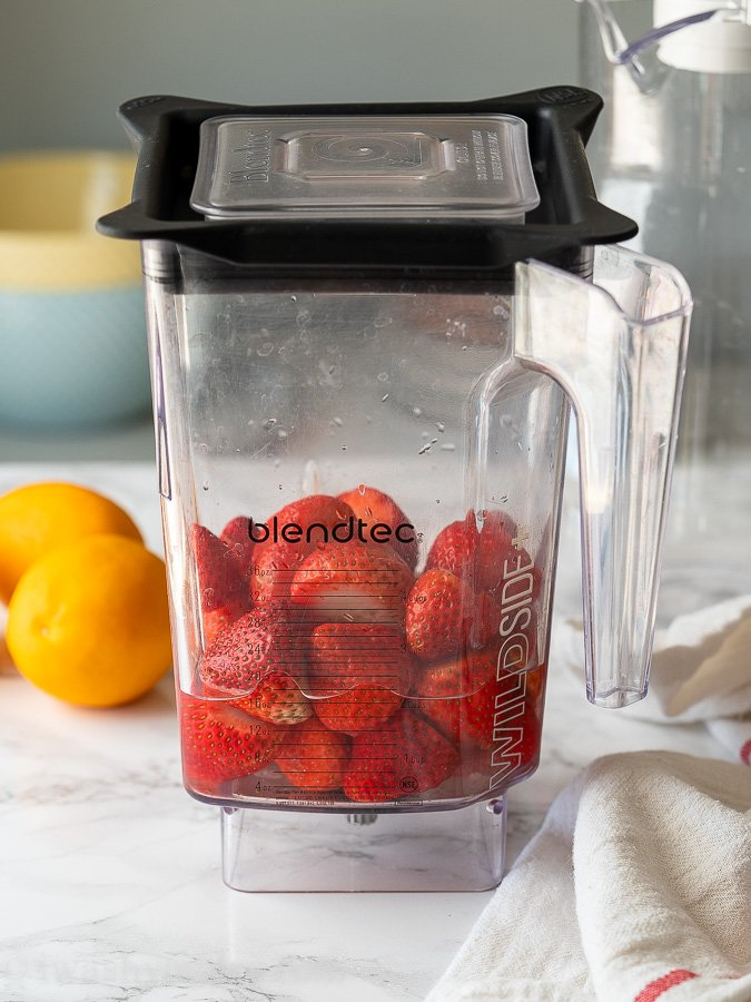 Place fresh or frozen strawberries in a blender or food processor to make the strawberry lemonade mixture.
