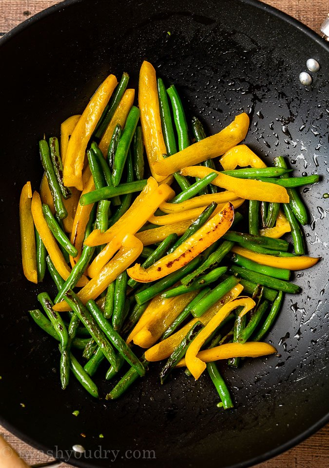 Sauté green beans and yellow peppers in a hot skillet until lightly charred.