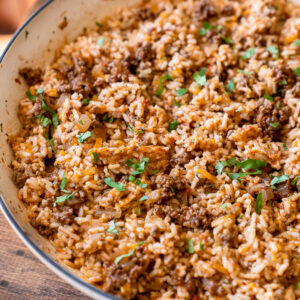 Close up shot of cheesy taco rice with bits of taco meat, gooey cheese and fresh cilantro on top.
