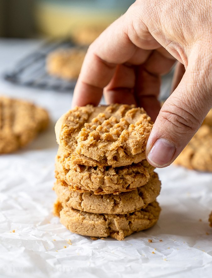 A stack of peanut butter cookies with a hand reaching down to grab one.