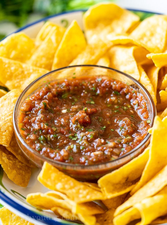 Bowl of restaurant style salsa with crispy tortilla chips surrounding it.