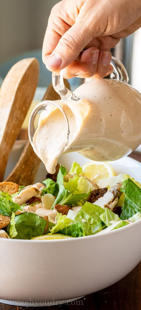 Homemade Caesar Salad Dressing being poured over chopped lettuce.