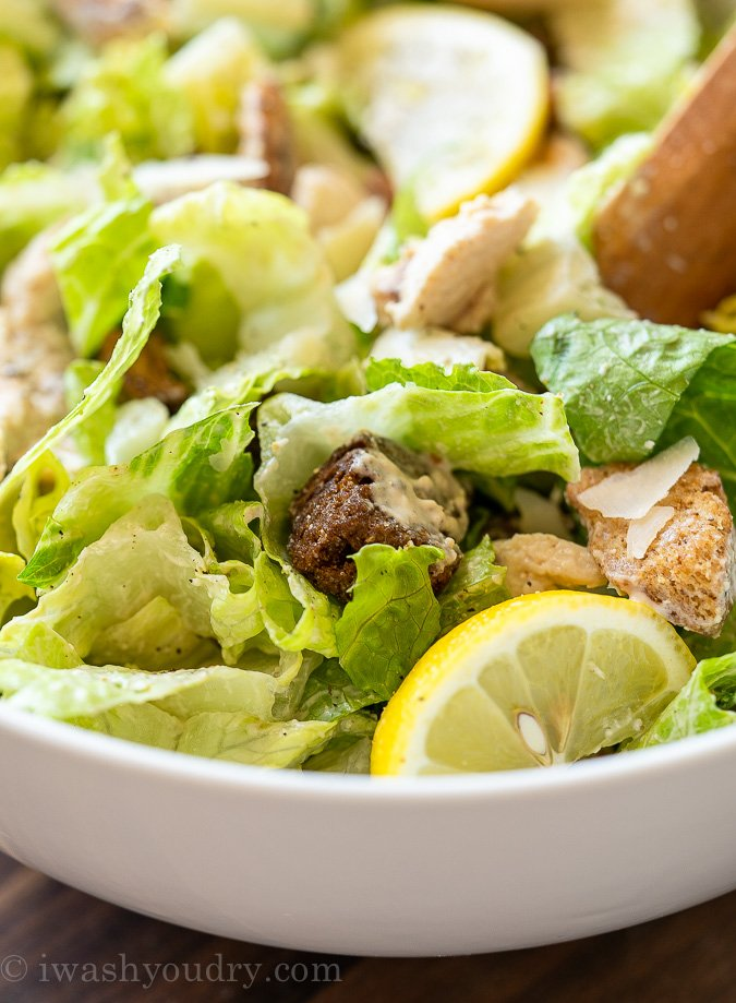 Bowl of crisp romaine lettuce and crunchy croutons and Caesar salad dressing on top