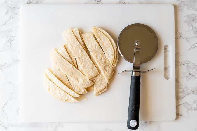 Strips of white corn tortillas with a pizza cutter beside them on a white cutting board.