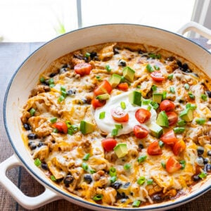 Skillet full of Chicken Black Bean Enchiladas, topped with sour cream, diced tomatoes and avocado!