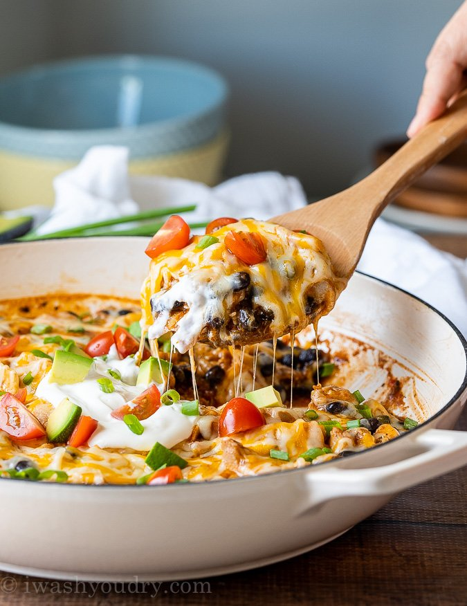 Spoonful of hearty Black Bean Enchiladas in a white pan.