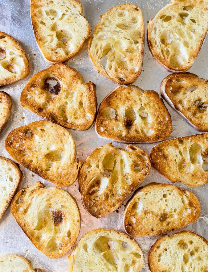 Toasted baguette pieces used for bruschetta topping.