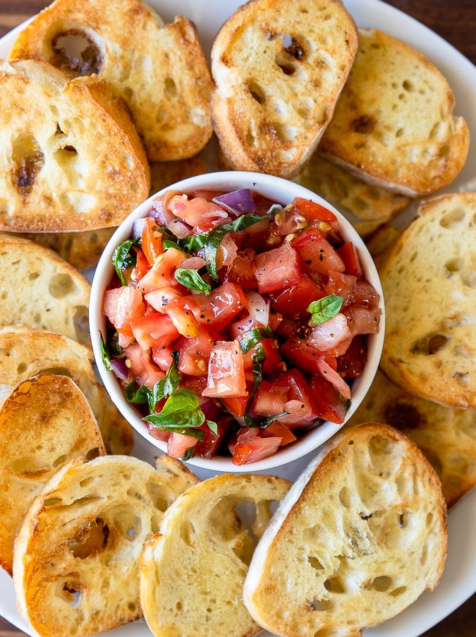 Small white bowl filled with tomato salad and toasted bread slices all around.