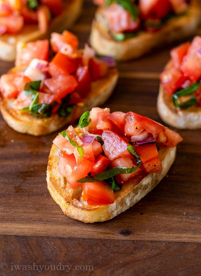 Close up image of simple bruschetta on top of a piece of toasted baguette bread.