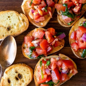 Slices of toasted baguette with fresh tomato bruschetta on top.