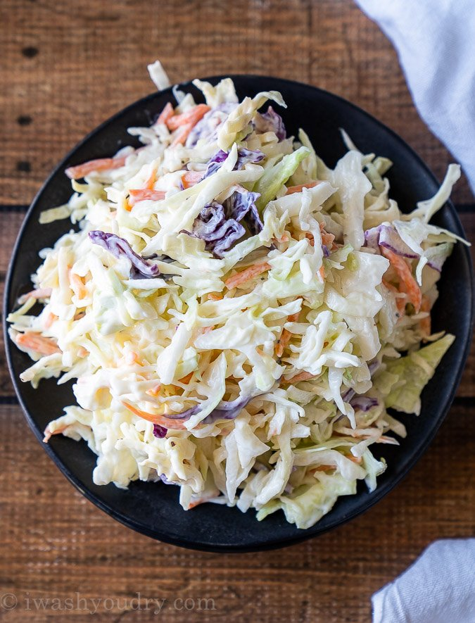 Top down picture of a black plate with coleslaw salad piled high.