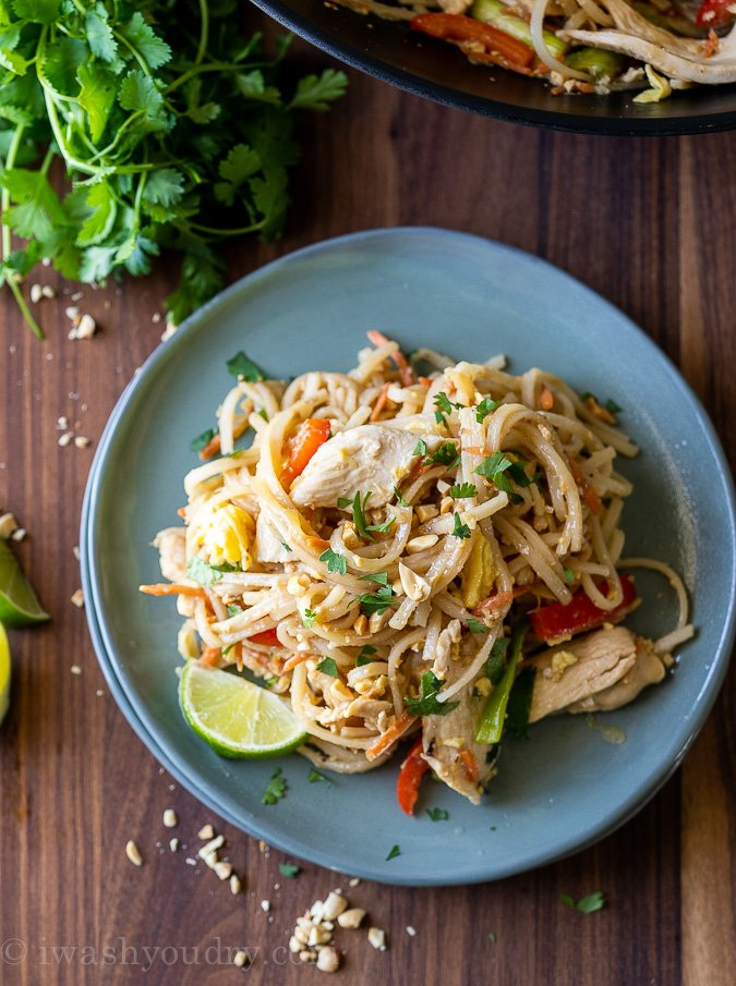 Simple Chicken Pad Thai recipe on a blue plate with lime wedge.