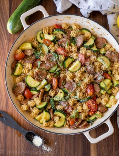 Chicken sausages, zucchini, tomatoes and pasta in a large skillet