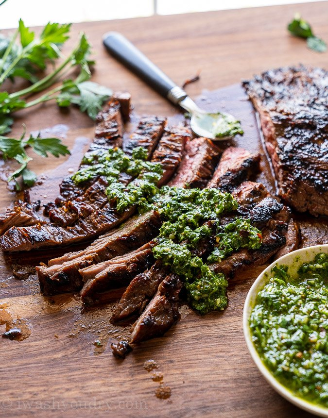 Sliced steak on a cutting board with green chimichurri sauce over the top.