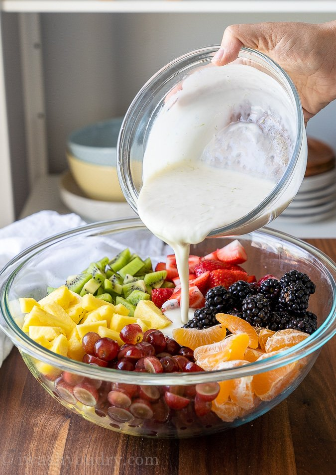 Creamy fruit salad dressing pouring over fresh fruits