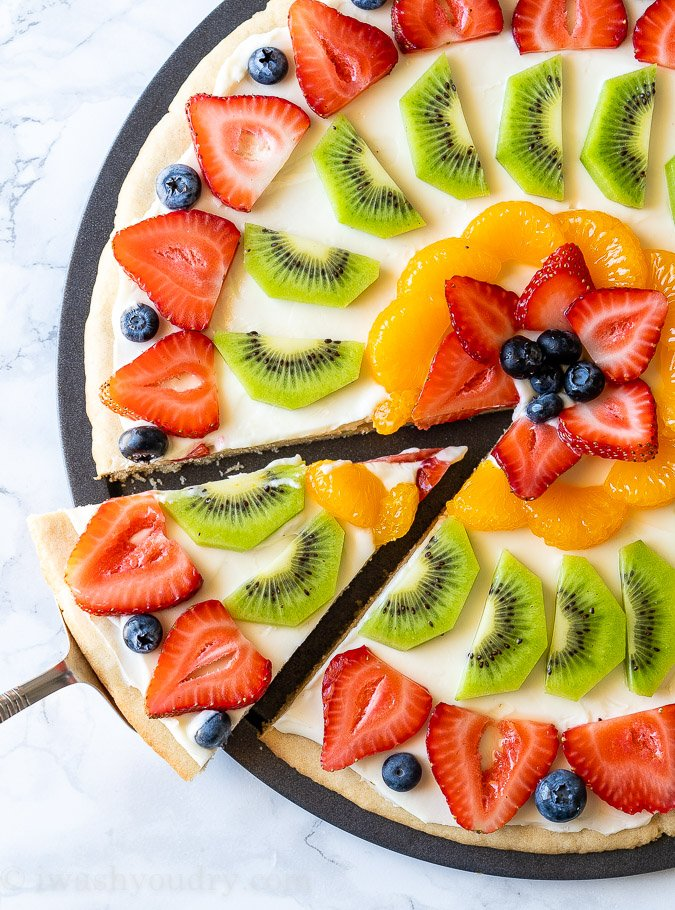 Sliced Fruit Pizza with cream cheese frosting and fresh fruits.