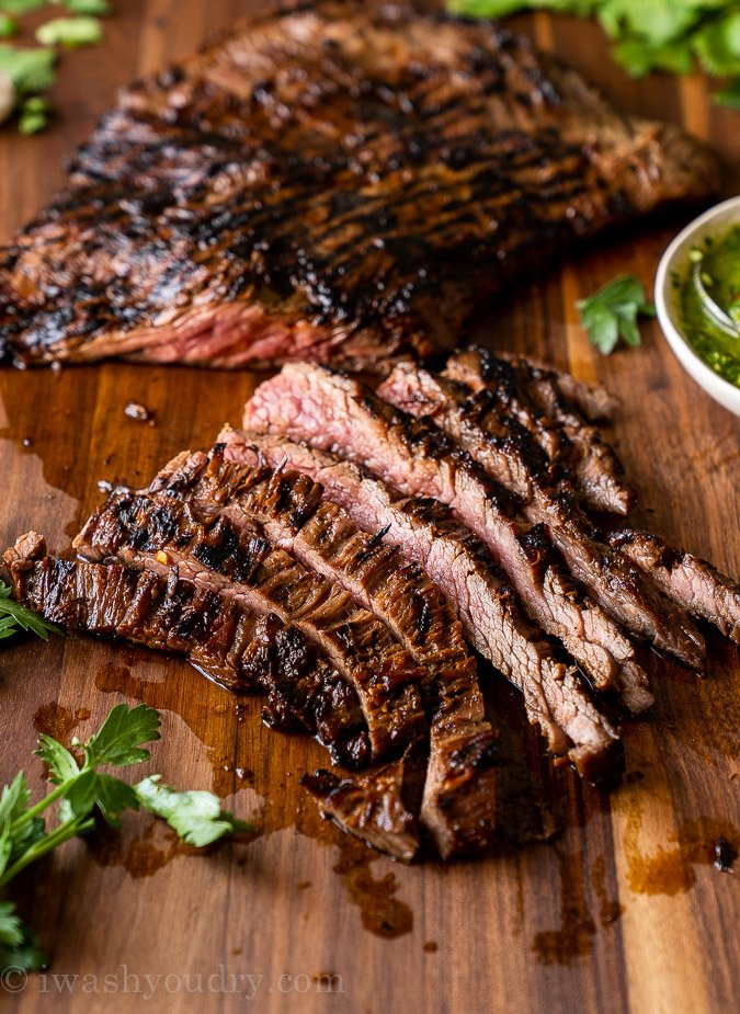 Thinly sliced skirt steak strips on a cutting board.