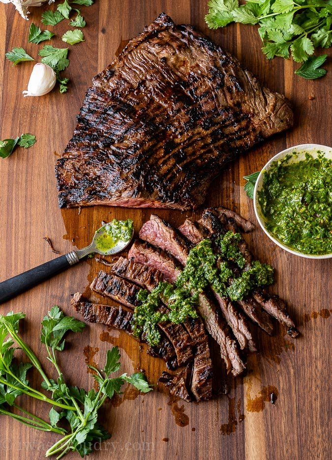 Grilled and sliced skirt steak on a cutting board with chimichurri sauce on top.